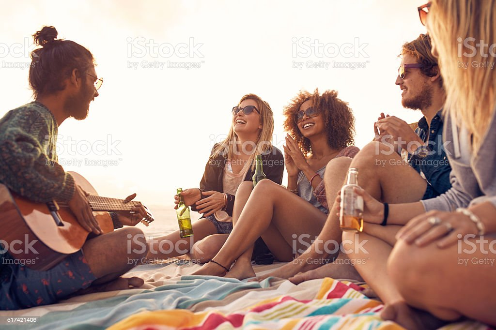 Group of smiling friends having fun at the beach stock photo