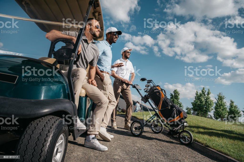 group of smiling friends standing near golf cart and looking away stock photo