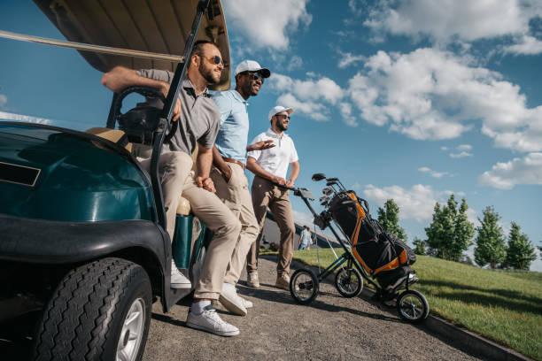 Groupe d'amis souriants debout près de voiturette de golf et à la recherche. - Photo