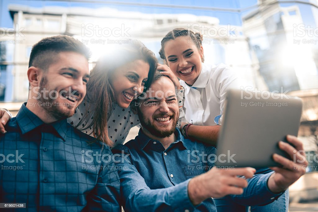 Group of Smiling Friends Surfing the Net in the City stock photo