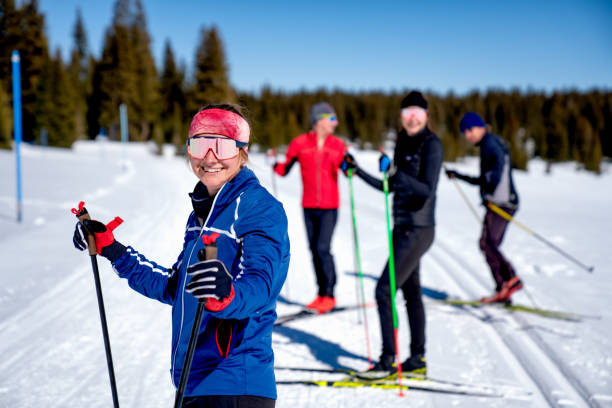 A Group Of Smiling Friends Taking A Break During A Cross Country Ski Trip stock photo