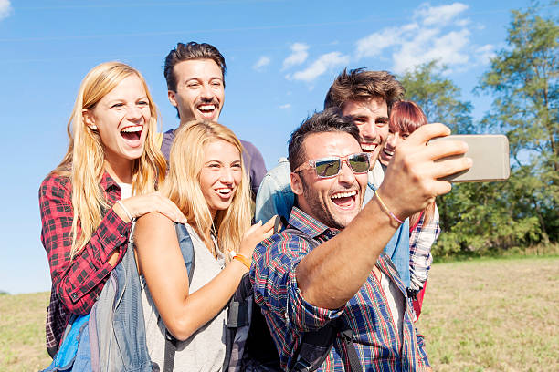 group of smiling friends taking selfie with smartphone stock photo