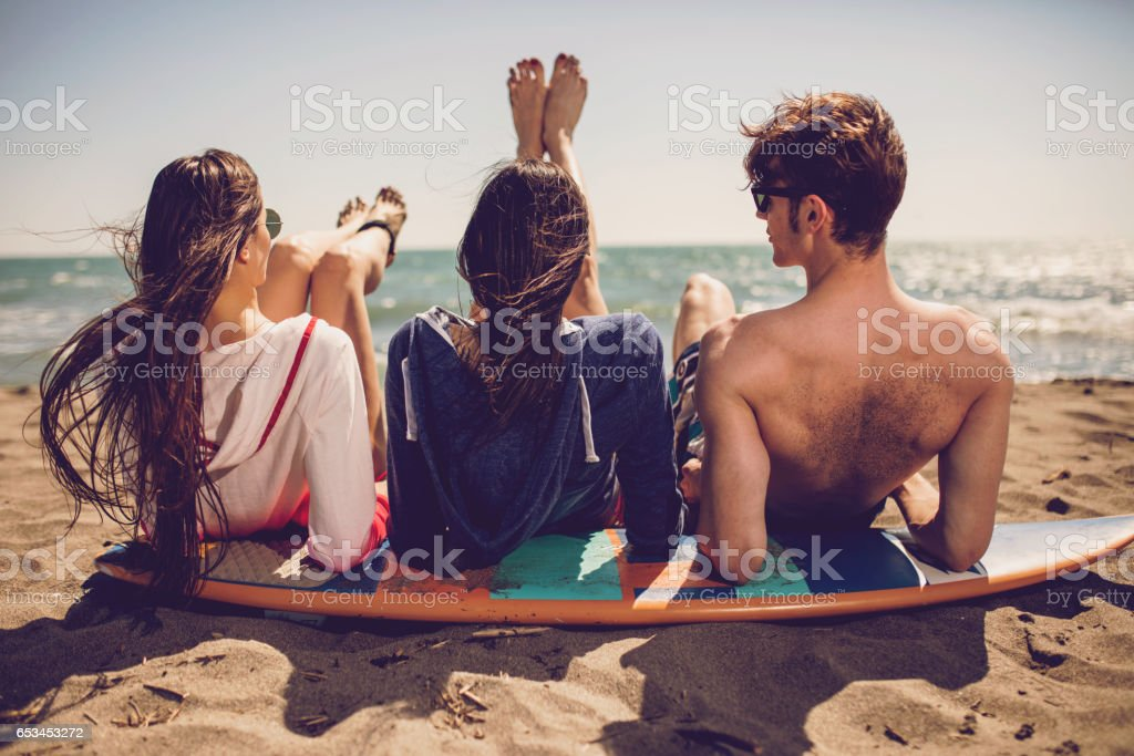 Group of smiling friends wearing swimwear and sunglasses with surfboards on beach. Summer concept, friends, friendship, summer fun, young people having fun stock photo