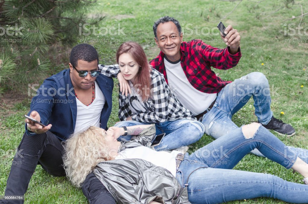 group of smiling friends with smartphones sitting on grass in park stock photo