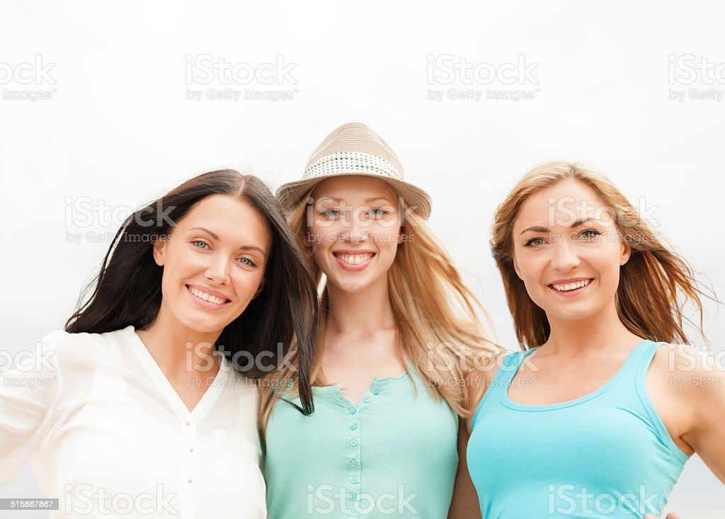 group of smiling girls chilling on the beach stock photo