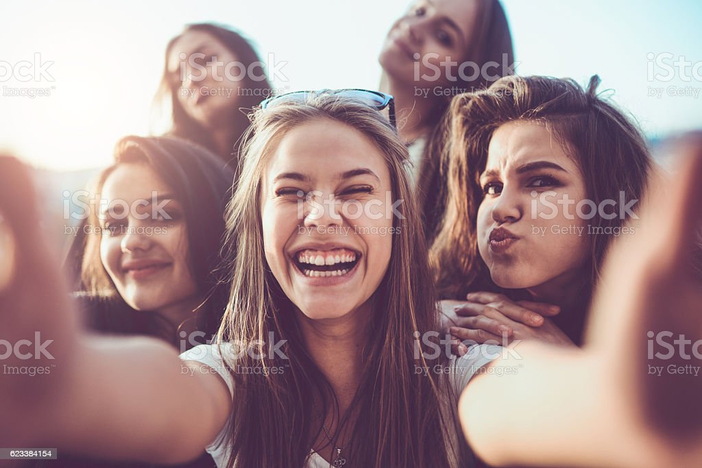 Group of Smiling Girls Taking a Selfie Outdoors at Sunset stock photo