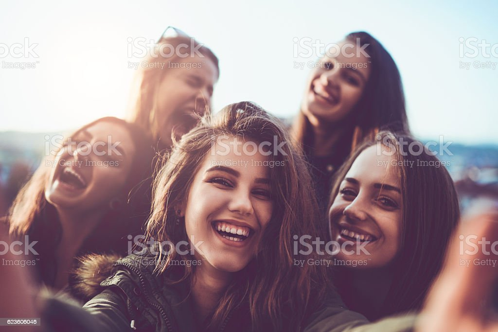 Group of Smiling Girls Taking a Selfie Outdoors at Sunset - foto stock