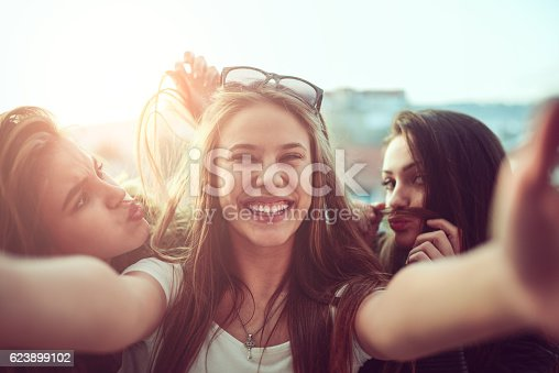 Group of teen friends how smiling, making faces and taking selfie with their mobile smartphone outdoor on the street at sunset.
