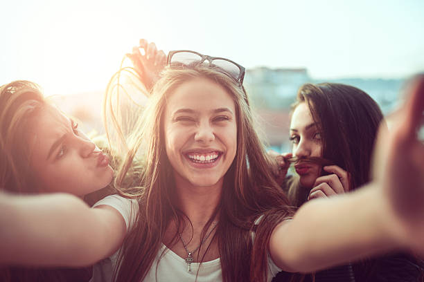 group of smiling girls taking funny selfie outdoors at sunset - city joke stock-fotos und bilder
