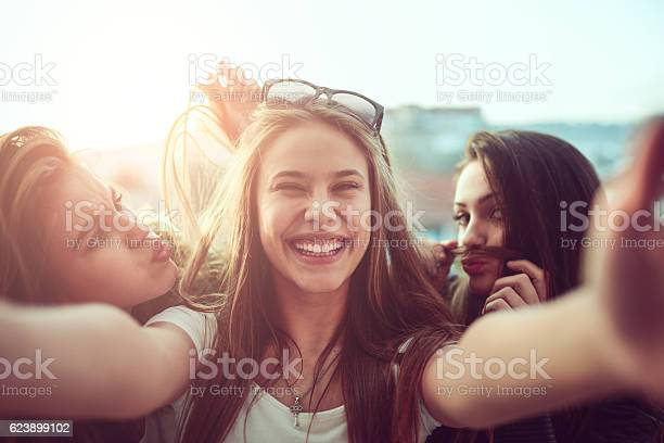 Photo of Group of Smiling Girls Taking Funny Selfie Outdoors at Sunset