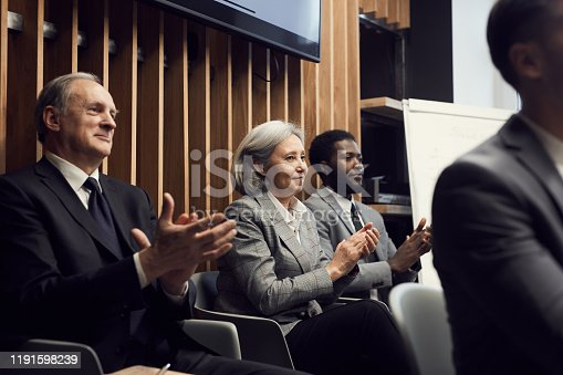 862720340 istock photo Group of smiling multi-ethnic business people of different ages sitting in row and clapping hands while greeting speaker at conference 1191598239