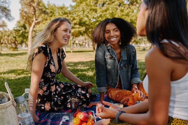 group of smiling multiracial female best friends sitting together on blanket with fruits enjoying at picnic in the park - group of healthy friends having a picnic - picnic foto e immagini stock