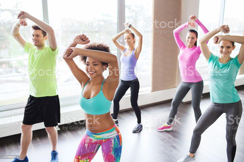 Gruppo di sorridenti persone ballare in palestra o monolocale - foto stock