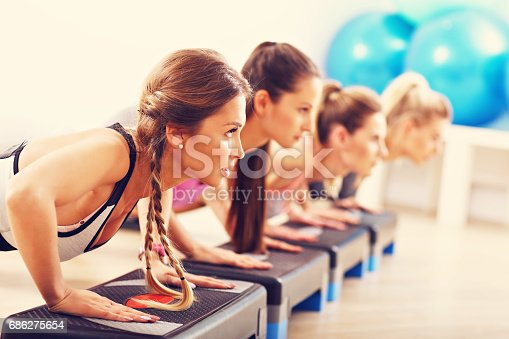 istock Group of smiling people doing push-ups 686275654