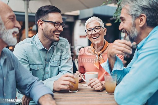 Group of people at different ages drinking and talking in cafe