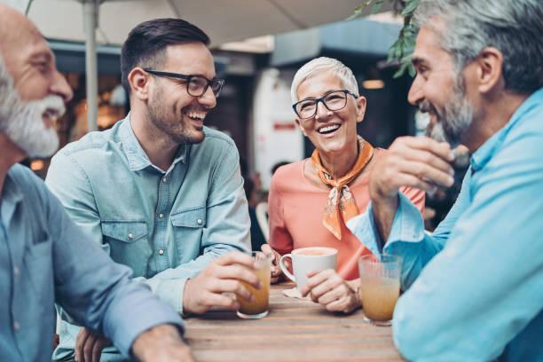 groep lachende mensen die in café praten - kleine groep mensen stockfoto's en -beelden
