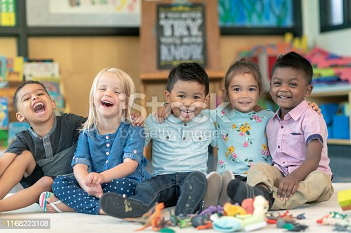 Portrait of a happy multi-ethnic group of preschool students in their classroom. The cute children are sitting in a line with their arms around each other. The kids are laughing and smiling directly at the camera.