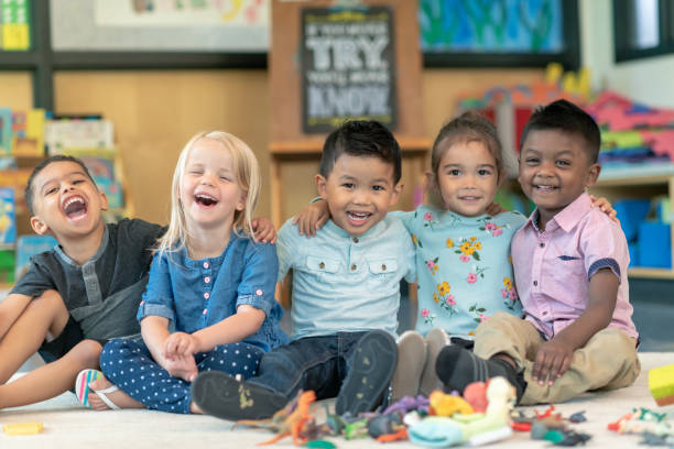 Group of smiling preschool students Portrait of a happy multi-ethnic group of preschool students in their classroom. The cute children are sitting in a line with their arms around each other. The kids are laughing and smiling directly at the camera. preschool age stock pictures, royalty-free photos & images