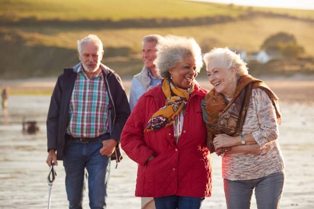 grupa uśmiechniętych starszych przyjaciół idących ramieniem w ramię wzdłuż linii brzegowej zimowej plaży - dojrzały zdjęcia i obrazy z banku zdjęć