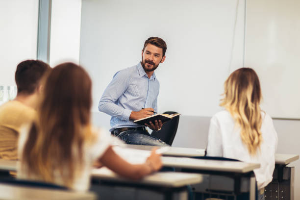 Group of smiling students and teacher with notebook in classroom stock photo