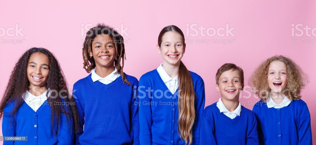 Group of smiling students Portrait of group of young students smiling against pink background. Children in school uniform standing together. 12-13 Years Stock Photo