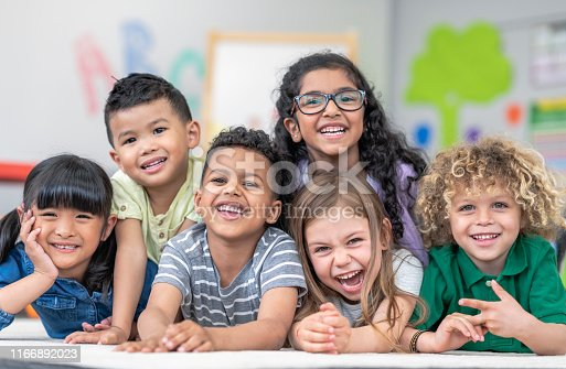 Portrait of a happy multi-ethnic group of kindergarten age students. The cute children are laying in a pile on the ground in a modern classroom. The kids are laughing and smiling.