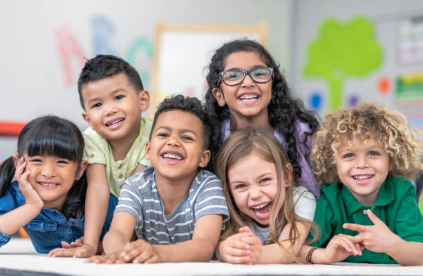 Group of smiling students Portrait of a happy multi-ethnic group of kindergarten age students. The cute children are laying in a pile on the ground in a modern classroom. The kids are laughing and smiling. preschool age stock pictures, royalty-free photos & images