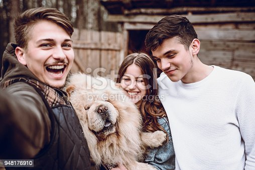 636418612 istock photo Group of Smiling Teenagers Take Selfie With Their Chow Chow Dog on Picnic 948176910