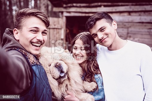 636418612 istock photo Group of Smiling Teenagers Take Selfie With Their Chow Chow Dog on Picnic 948503274