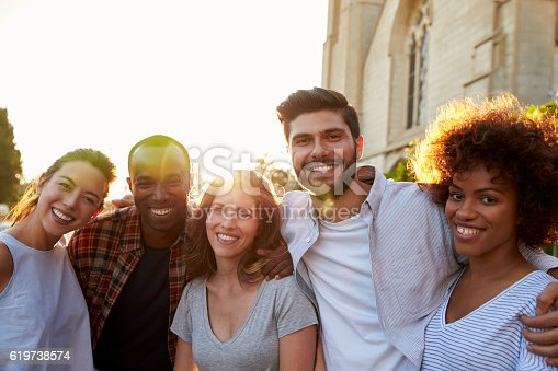 istock Group of smiling young adult friends embracing in the street 619738574