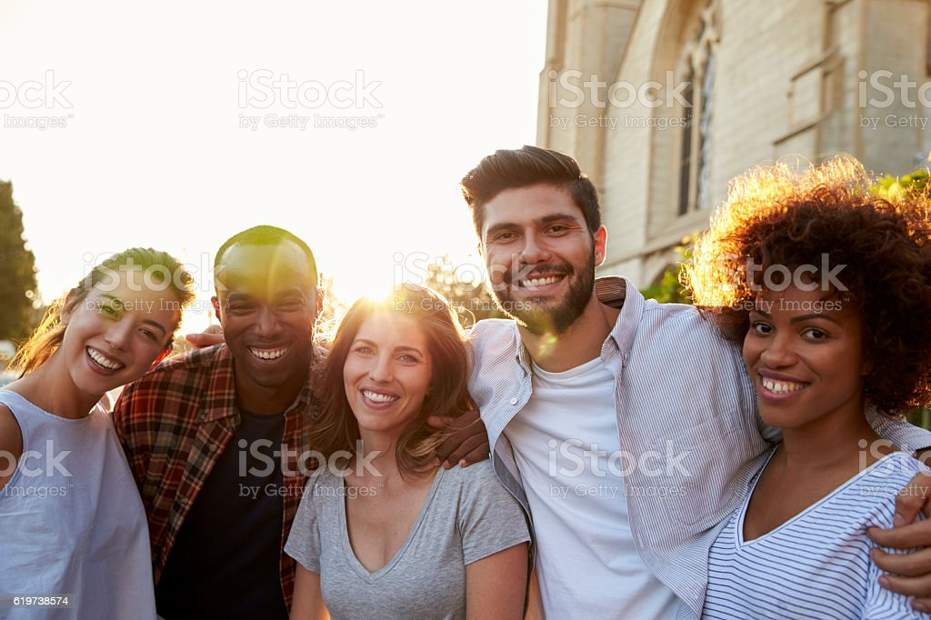 Group of smiling young adult friends embracing in the street stock photo