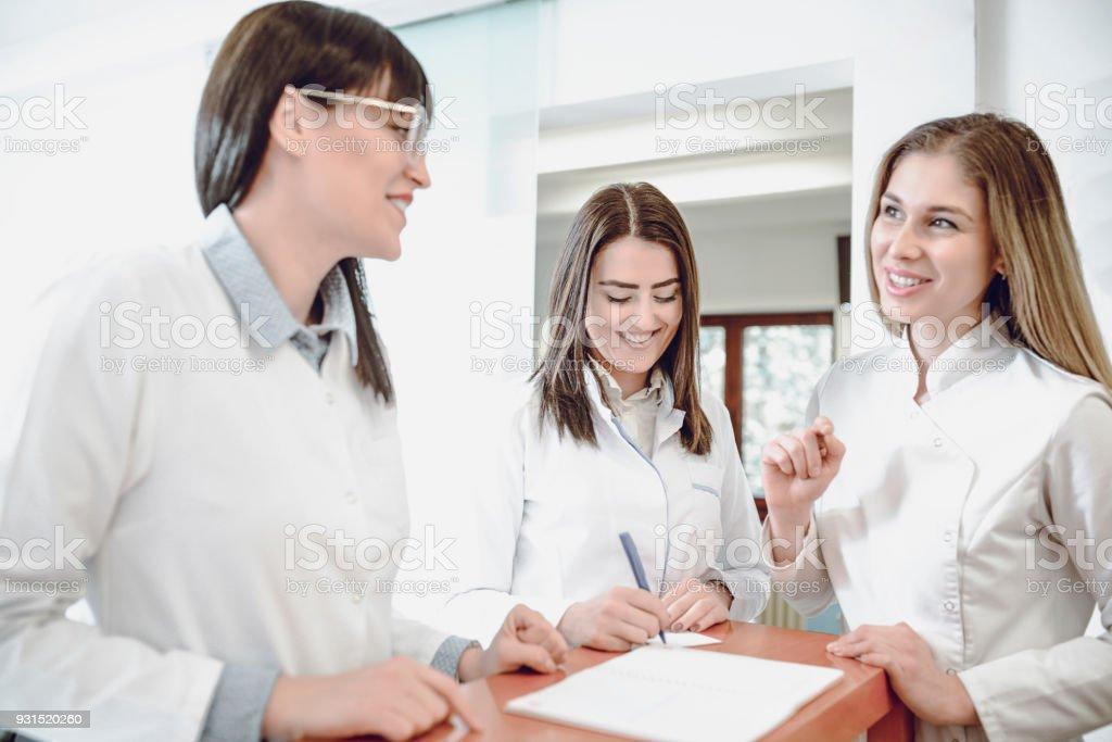 Gruppe von lächelnden junge Ärztinnen im Gespräch an der Rezeption in Klinik - Lizenzfrei Allgemeinarztpraxis Stock-Foto