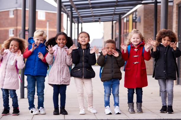 genç çok etnik gruptan oluşan okul gülümseyen bir grup giyiyor kat ve taşıma okul ayakta sallayarak kamera, tam uzunlukta, önden görünüm için onların çocuk okul dışında geçit bir satırda çocuklar - mont stok fotoğraflar ve resimler