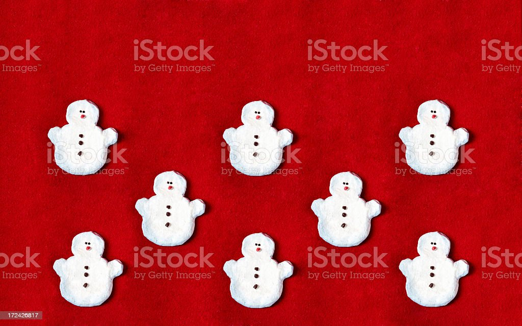 group of snowmen on the red wool background royalty-free stock photo