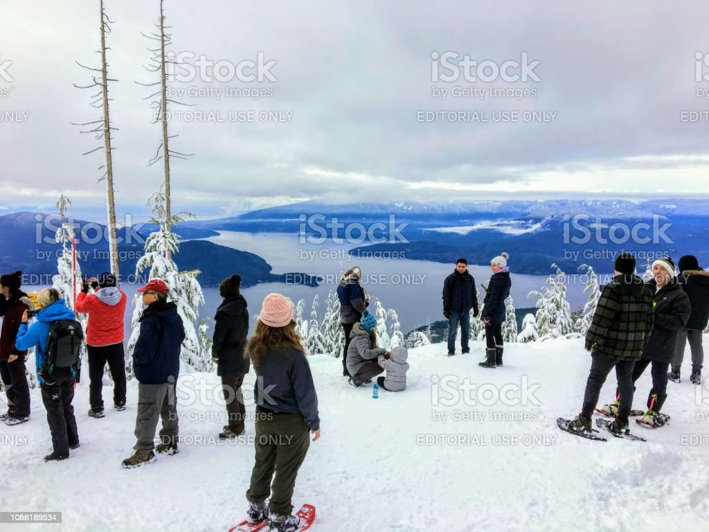 A group of snowshoers admiring the beautiful ocean views of Howe Sound stock photo