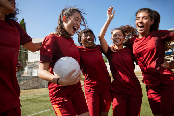 Group of soccer players celebrating huddled in circle stock photo