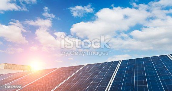 Group of solar panels against blue sky.
