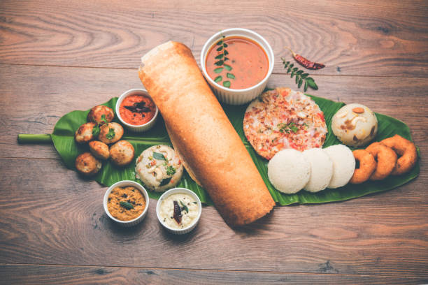 group of south indian food like masala dosa, uttapam, idli/idly, wada/vada, sambar, appam, semolina halwa, upma served over banana leaf with colourful chutneys, selective focus - south stock pictures, royalty-free photos & images
