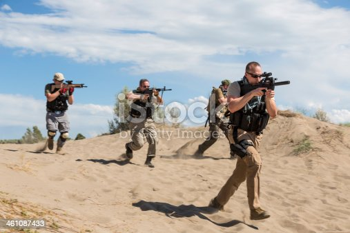 istock Group of special forces soldiers advancing with weapons drawn 461087433