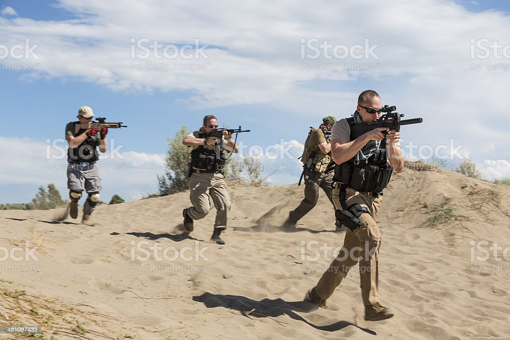 Group of special forces soldiers advancing with weapons drawn stock photo