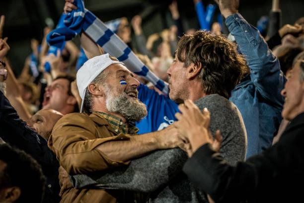 zuschauergruppe jubelt im stadion - fussball fan stock-fotos und bilder
