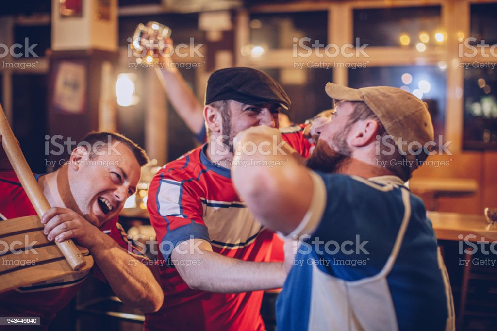 Group of sport fans fighting in sports bar stock photo