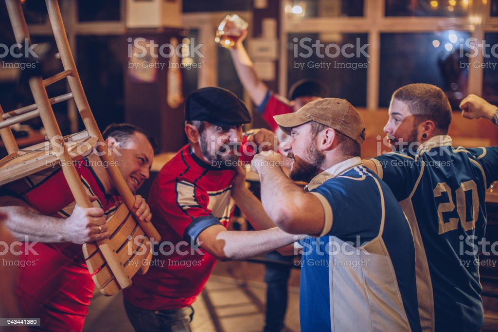 Group of sport fans fighting in sports pub stock photo