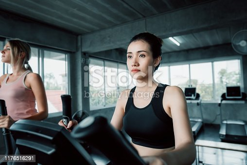 Group of Sport Women Exercising With Cycling Bike Machine in Fitness Club, Beautiful of Strong Women Doing Workout Exercised Weight Loss With Biking Equipment in Gym. Healthy Sport/Fitness Lifestyle