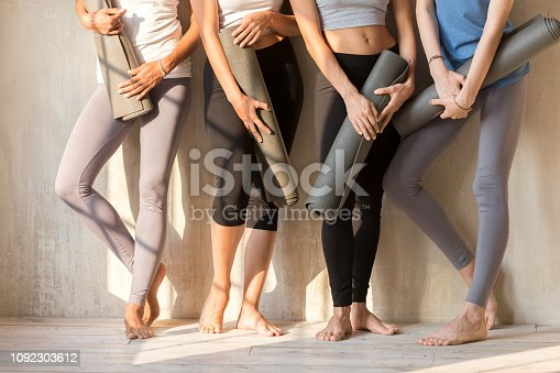 Barefoot legs feets of sportive young caucasian women in sportswear. Girls standing in a row near wall holding yoga mats rubber carpets, four females before or after sports workout at fitness studio