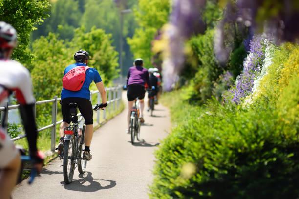 Grupo de hombre deportivo, ciclismo en Parque soleado día de verano caliente - foto de stock