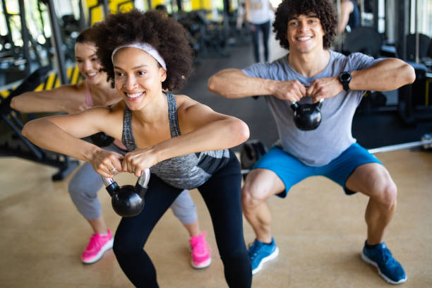 Group of sportive people in a gym training Group of sportive young people in a gym training cardiovascular exercise stock pictures, royalty-free photos & images