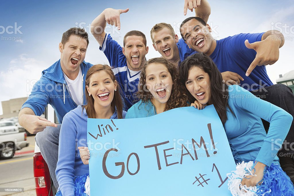 Group of sports fans cheering on team while tailgating stock photo