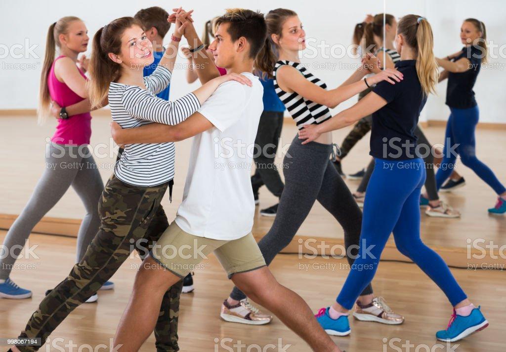 Group of sports teen learning to dancing tango in dance studio