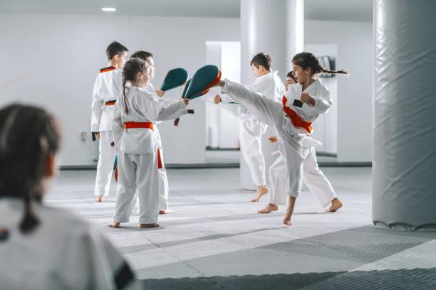 gruppe von sportlichen kaukasischen kindern in doboks, die taekwondo-klasse in weißen fitnessstudios. - taekwondo stock-fotos und bilder